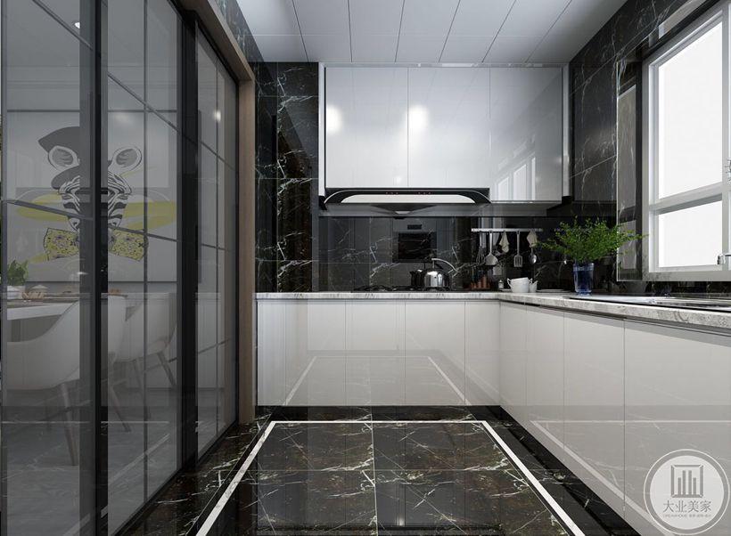 厨房的墙面地面都采用黑色瓷砖,橱柜都采用白色,操作台面采用白色大理石。